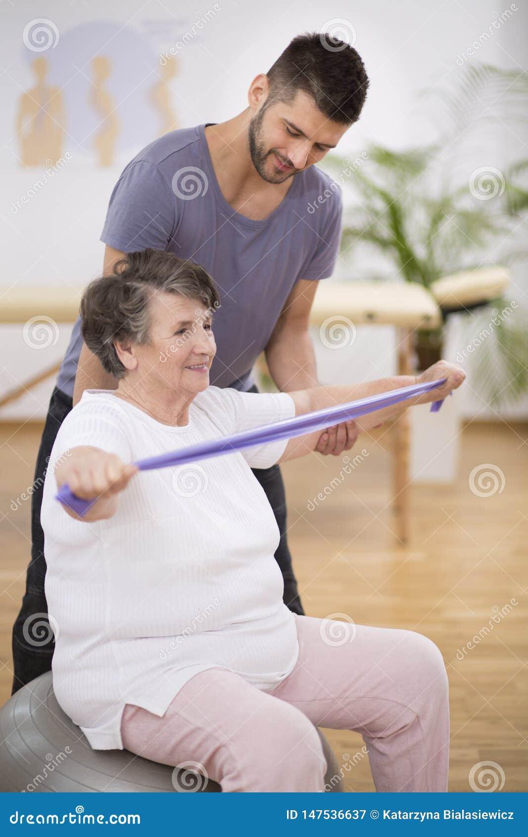 Bejaarde die met het uitrekken van banden met haar fysiotherapeut uitoefenen