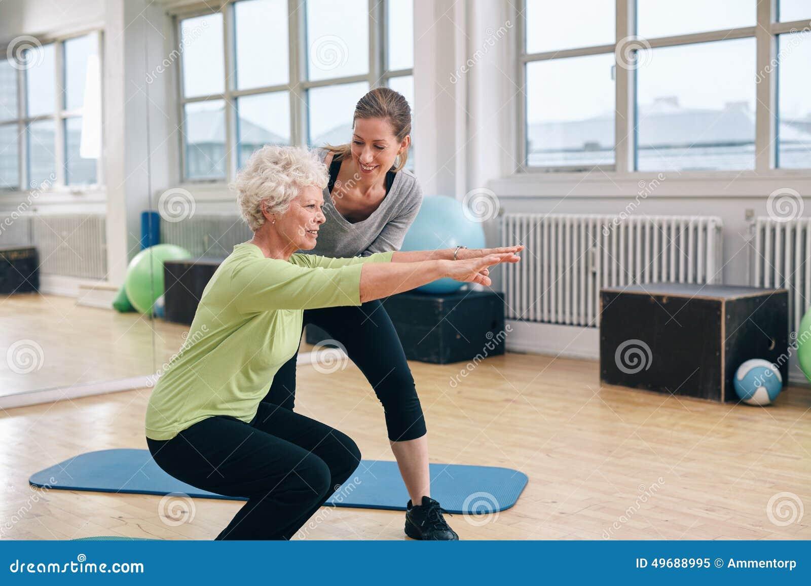 Bejaarde die oefening met haar persoonlijke trainer doen