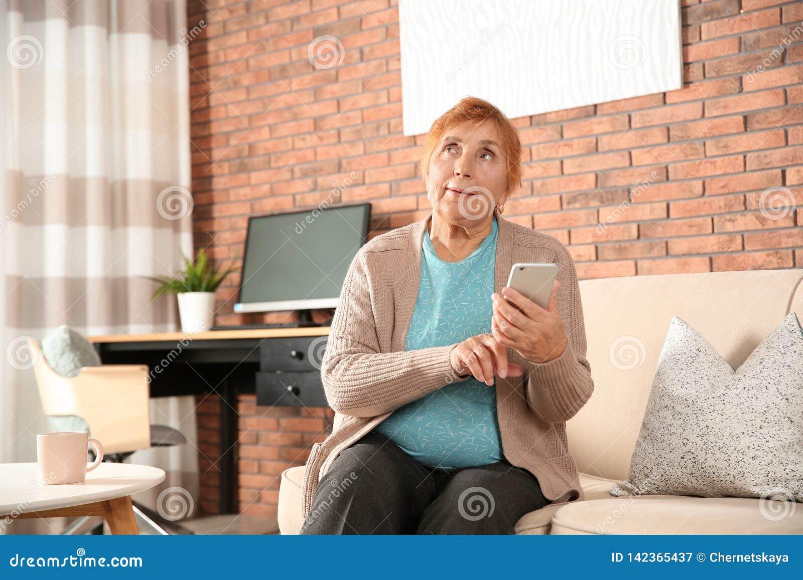 Bejaarde die smartphone op bank gebruiken