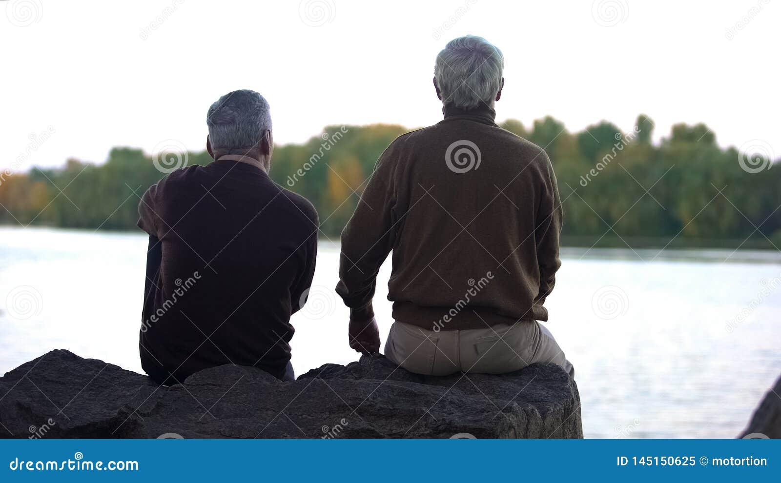 Bejaarde gepensioneerden die bos en water van zitting op rivierbank genieten, weekendrust