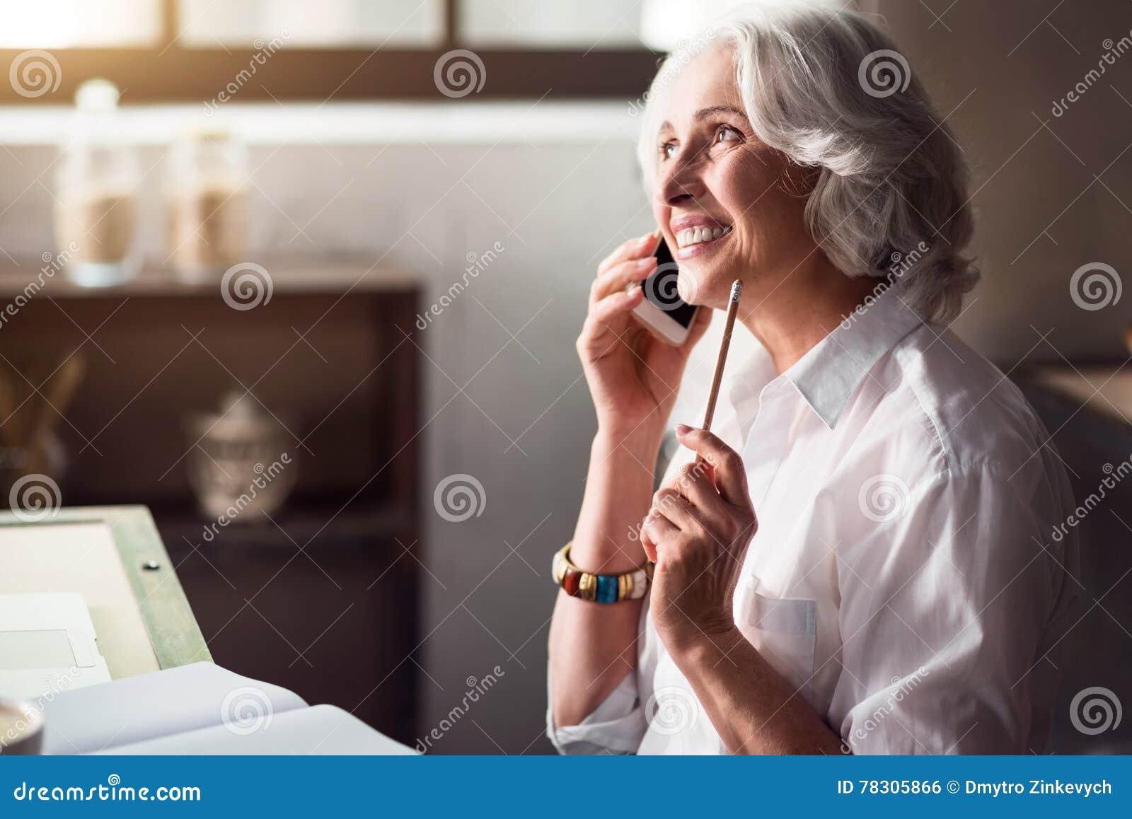 Bejaarde glimlachende vrouw die op de telefoon spreken