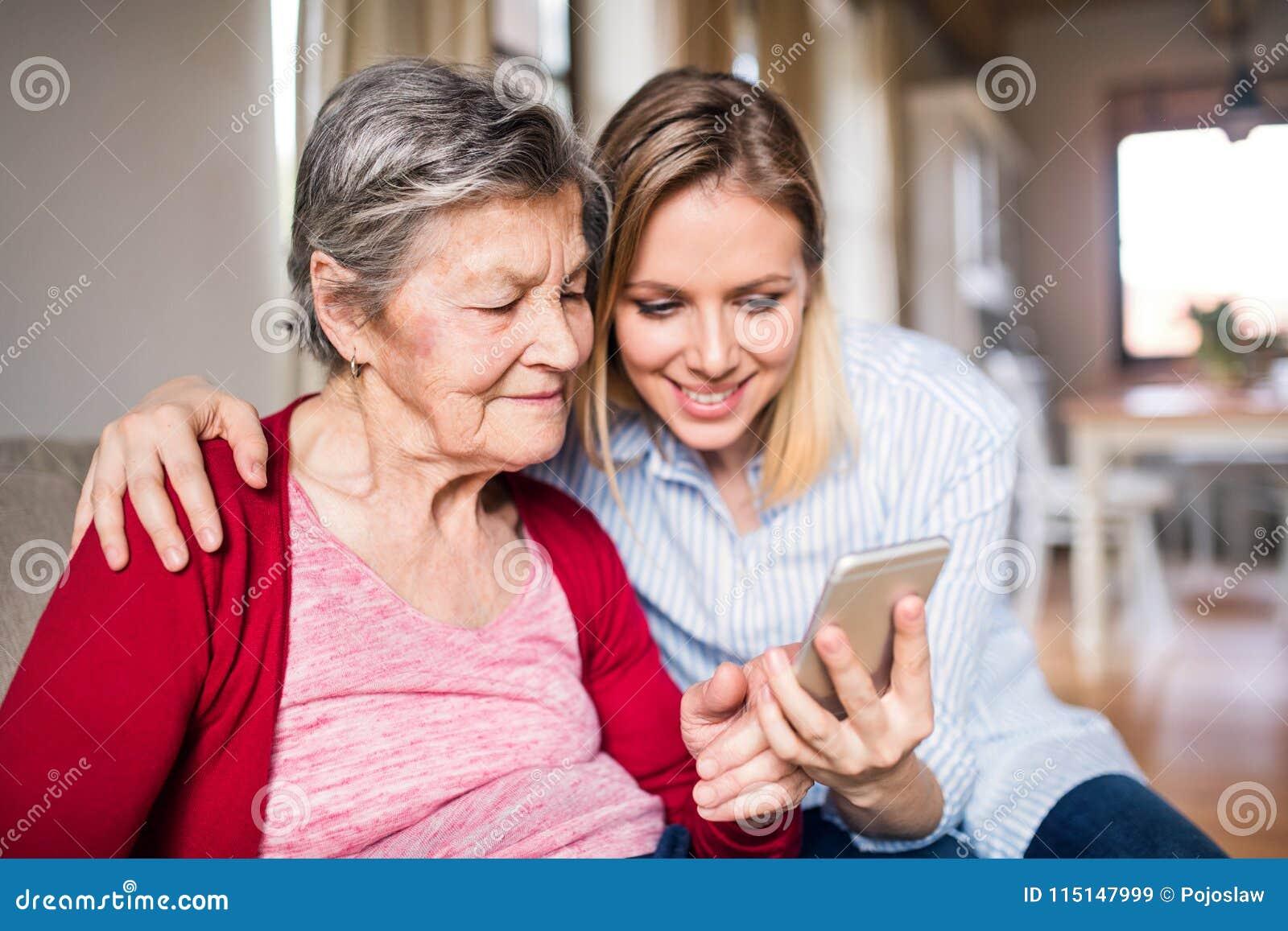 Bejaarde grootmoeder en volwassen kleindochter met smartphone thuis