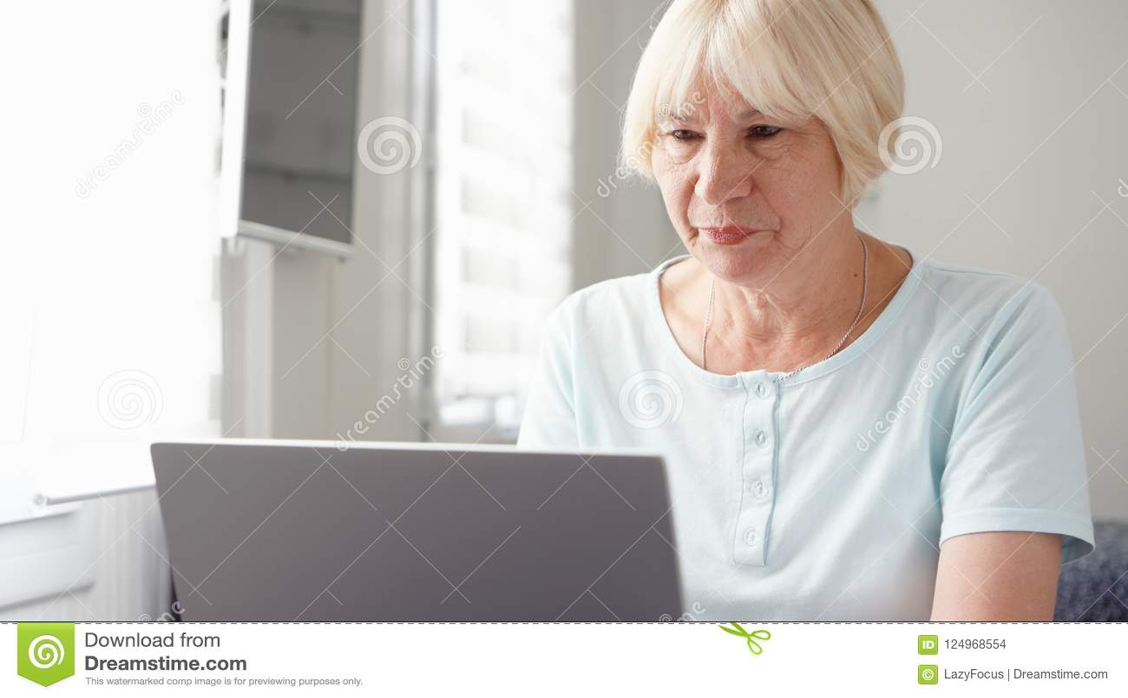 Bejaarde hogere blonde vrouw die aan laptop computer thuis werken Het verre freelance werk aangaande pensionering