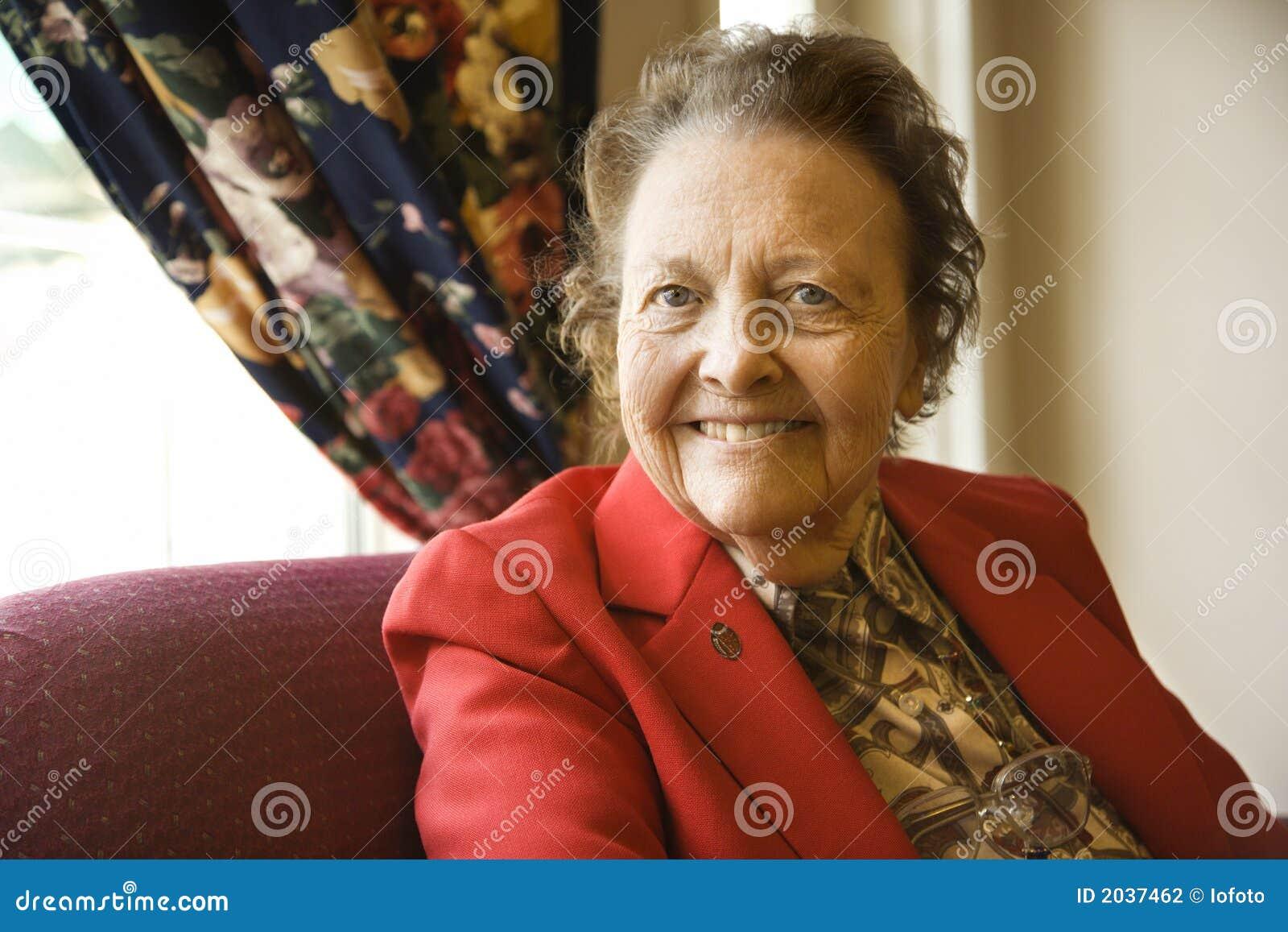 Bejaarde Kaukasische vrouw door venster.