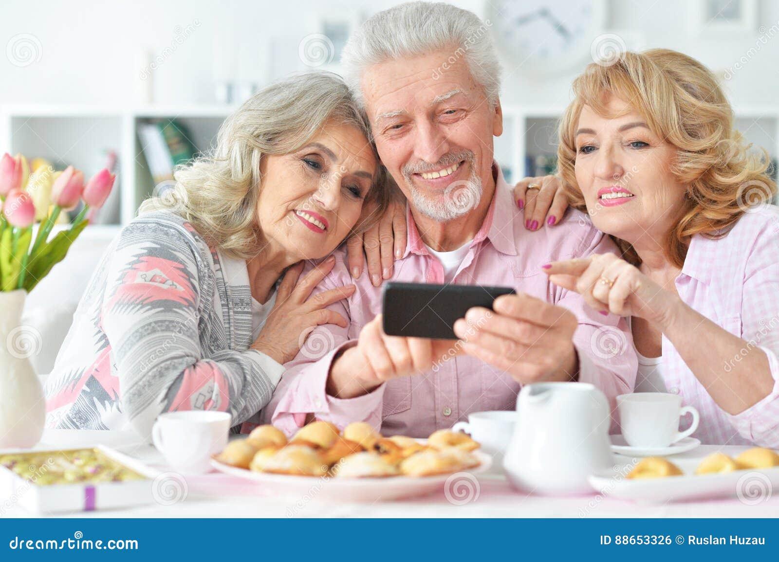 Bejaarde mensen die ontbijt hebben en mobiele telefoon met behulp van