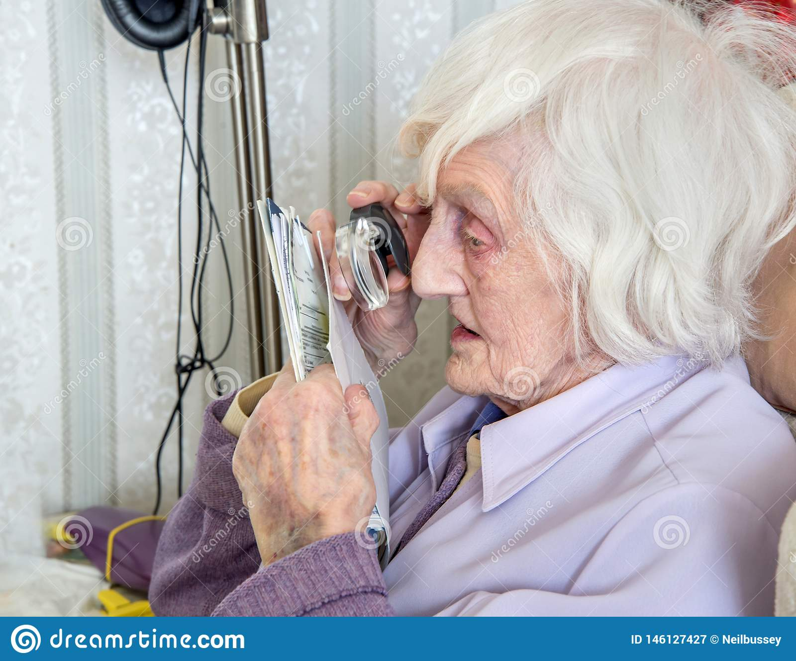Bejaarde met gezichtsstoornissen met magnifyer