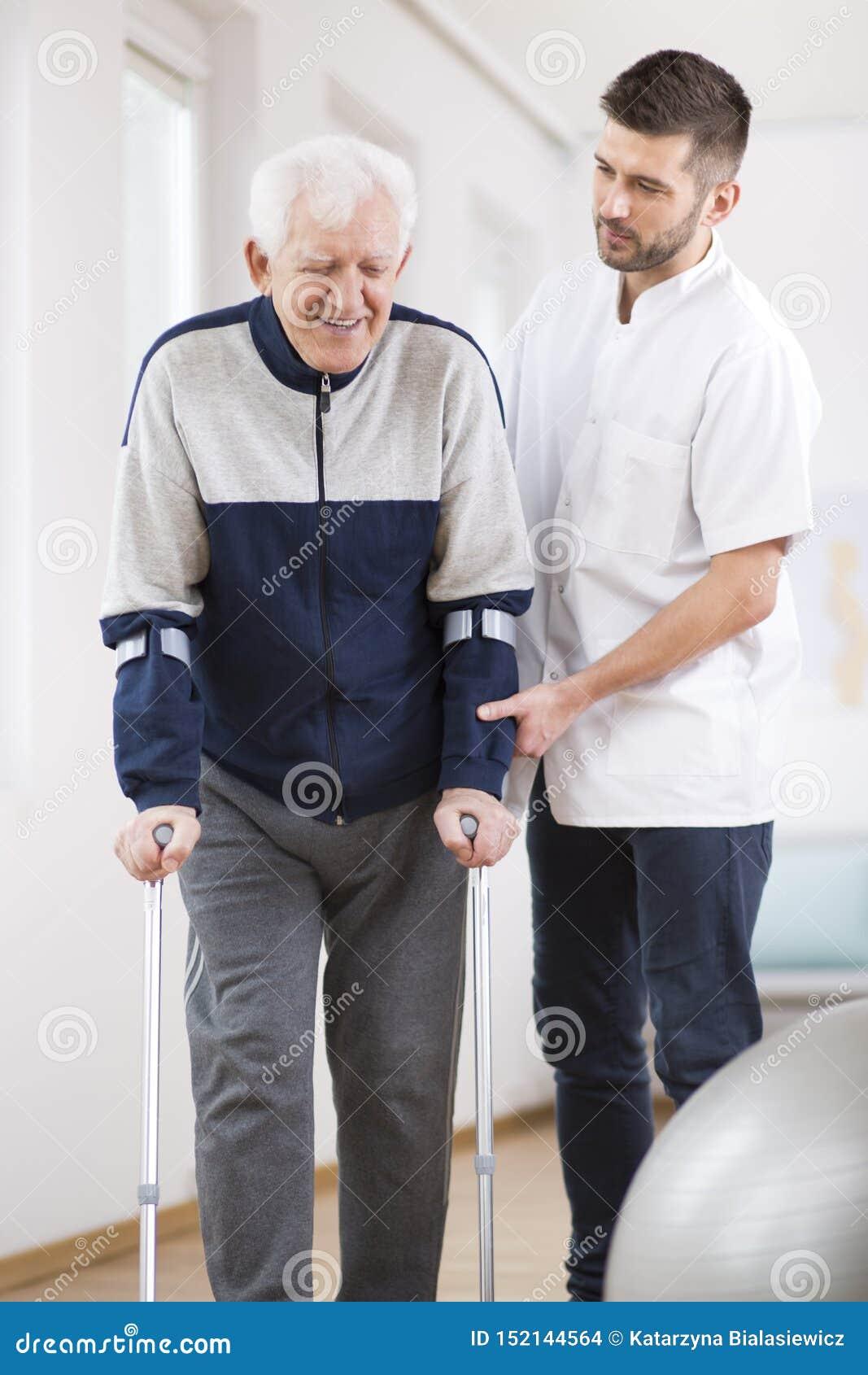 Bejaarde op steunpilaren lopen en een nuttige verpleger die ondersteunend hem