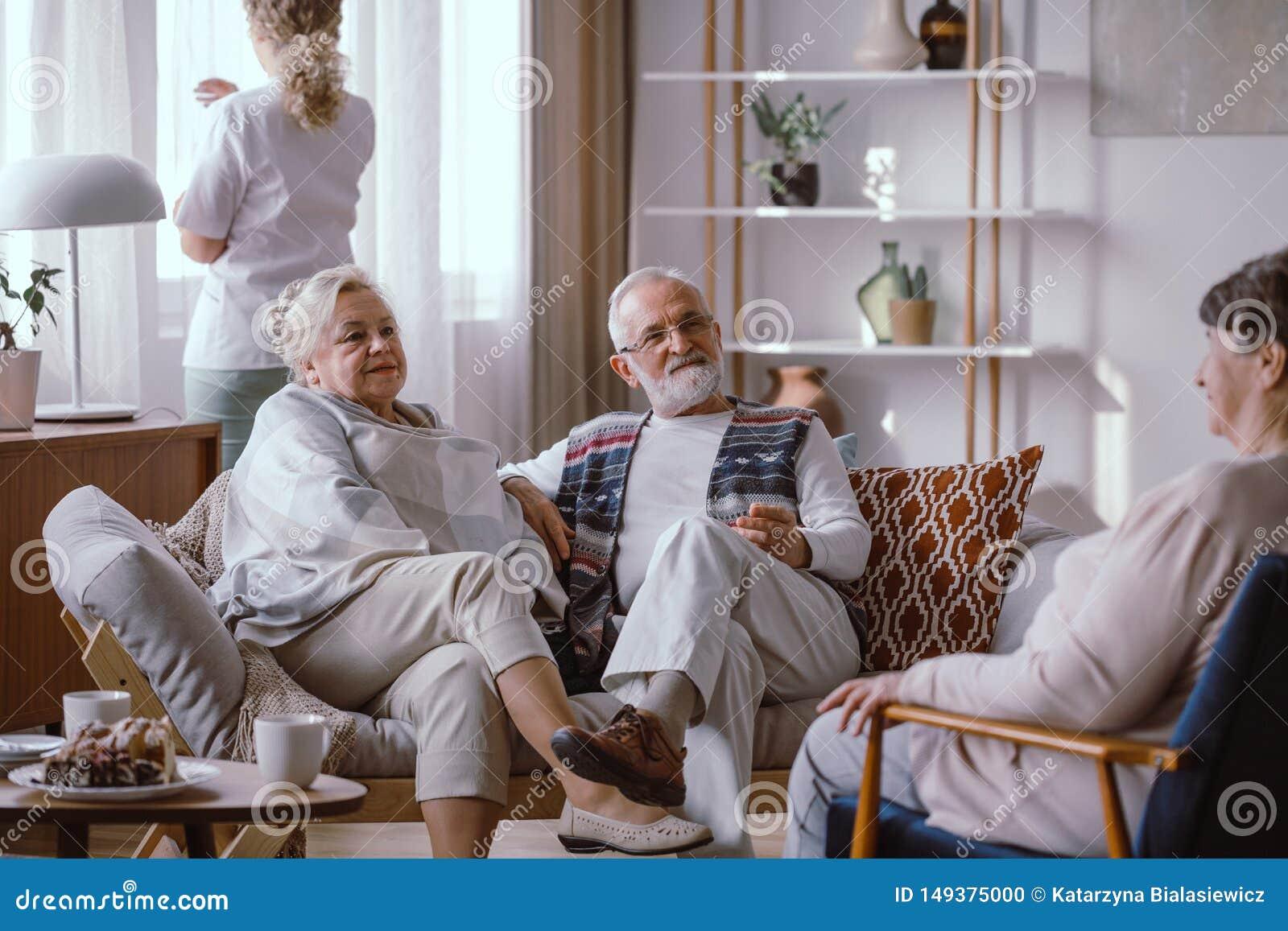 Bejaarde paarzitting op de bank in het verpleeghuis