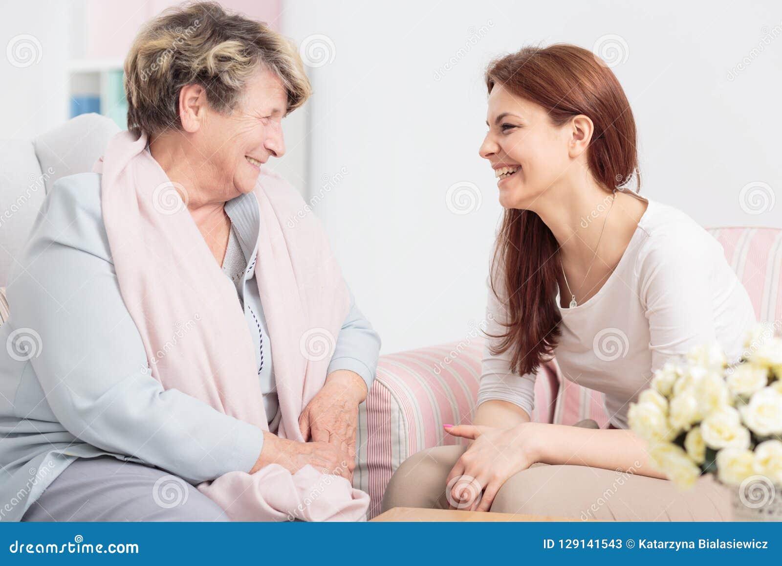 Bejaarde tijdens vergadering met vriendschappelijke verpleegster tijdens thuis het samenkomen