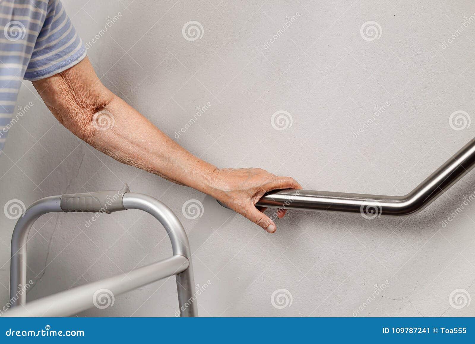 Bejaardeholding op leuning voor veiligheidsstappen