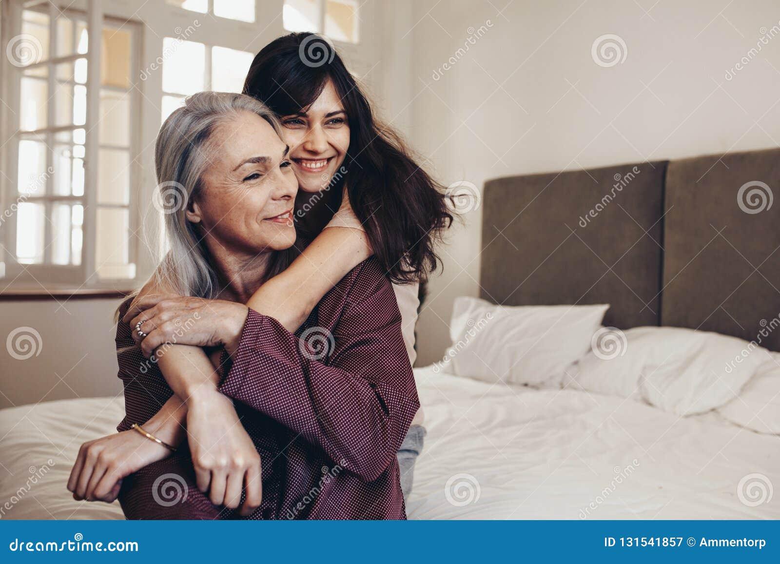 Bejaarden die op bed met haar dochter zitten die haar handen houden Glimlachende moeder en dochterzitting die thuis tijd doorbren