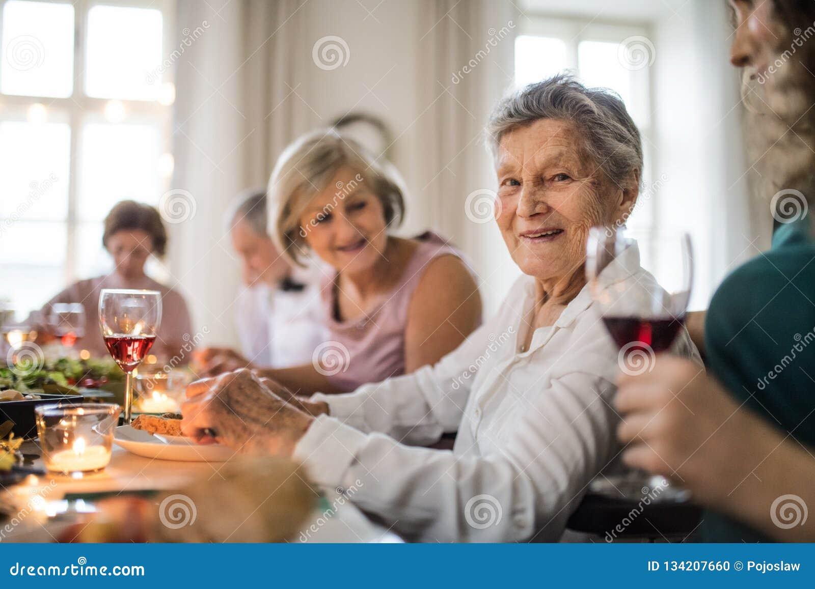 Bejaarden met een familiezitting bij een lijst aangaande een binnenpartij van de familieverjaardag