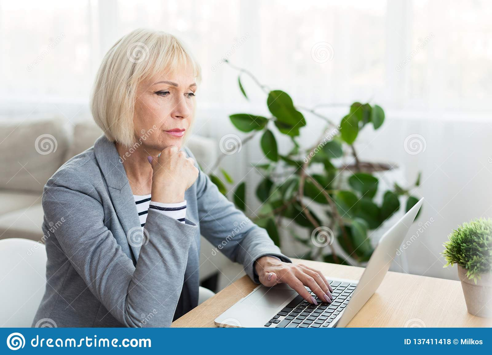 Bejaardeschrijver in het witte werken aan nieuw artikel