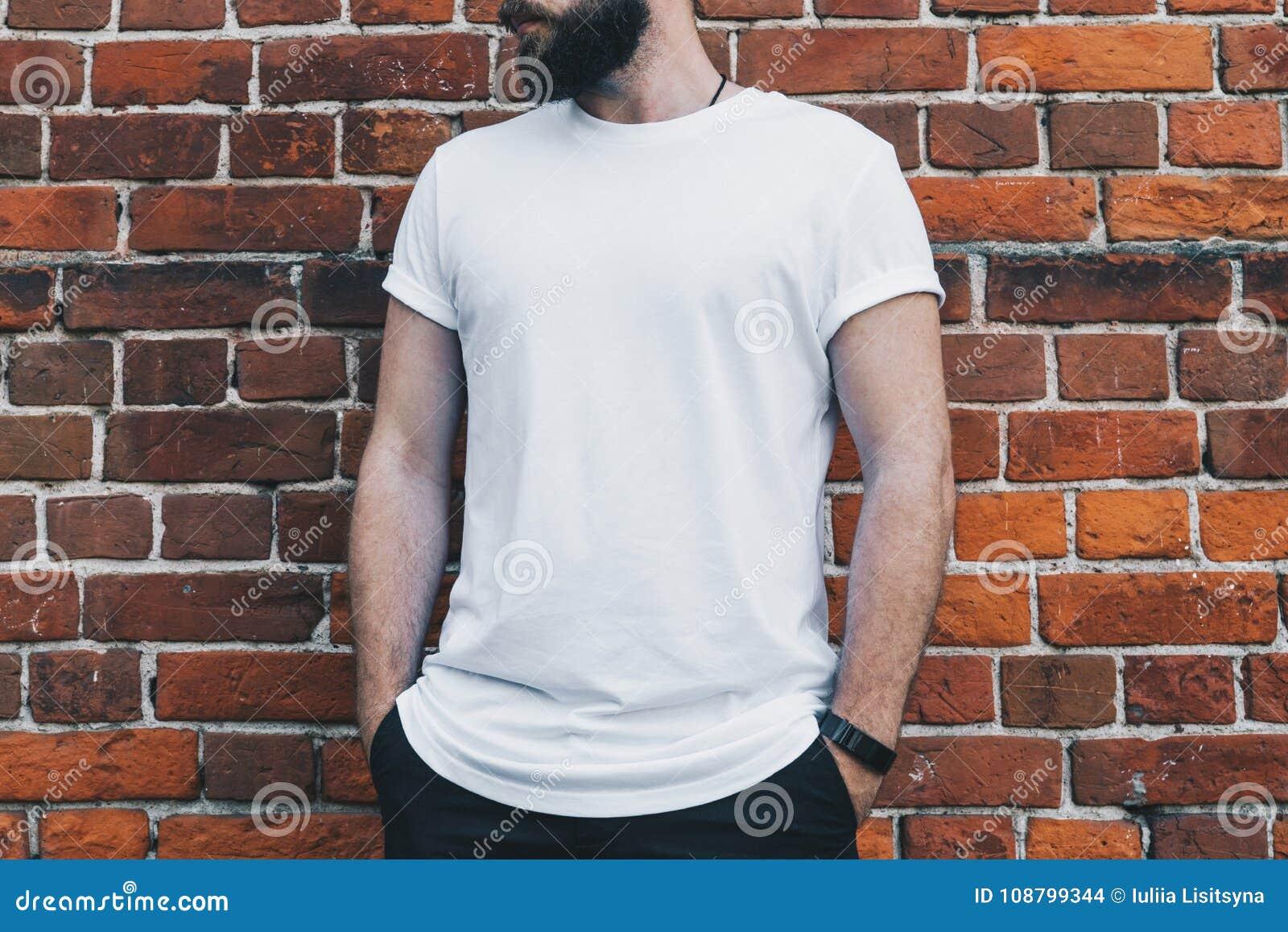 Bekläda beskådar Barnet uppsökte den millennial mannen som t-skjortan för iklädd vit är ställningar mot den mörka tegelstenväggen