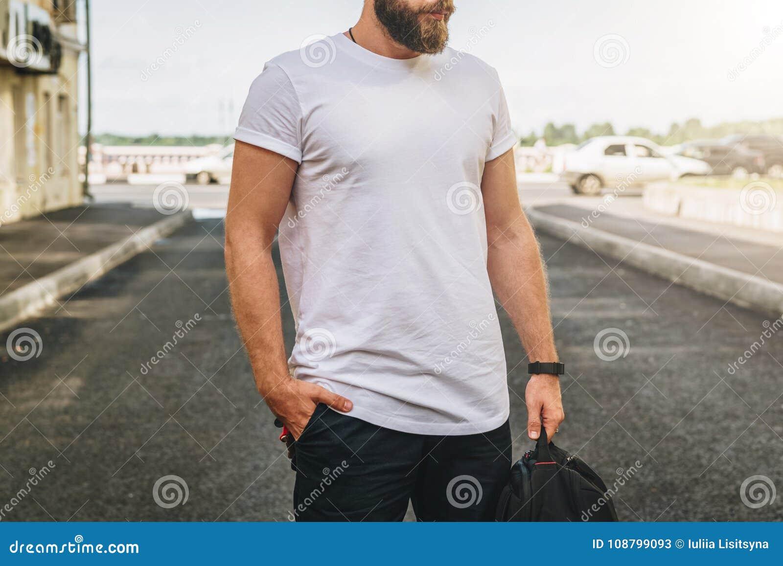 Bekläda beskådar Barnet uppsökte den millennial mannen som t-skjortan för iklädd vit är ställningar på stadsgatan Åtlöje upp