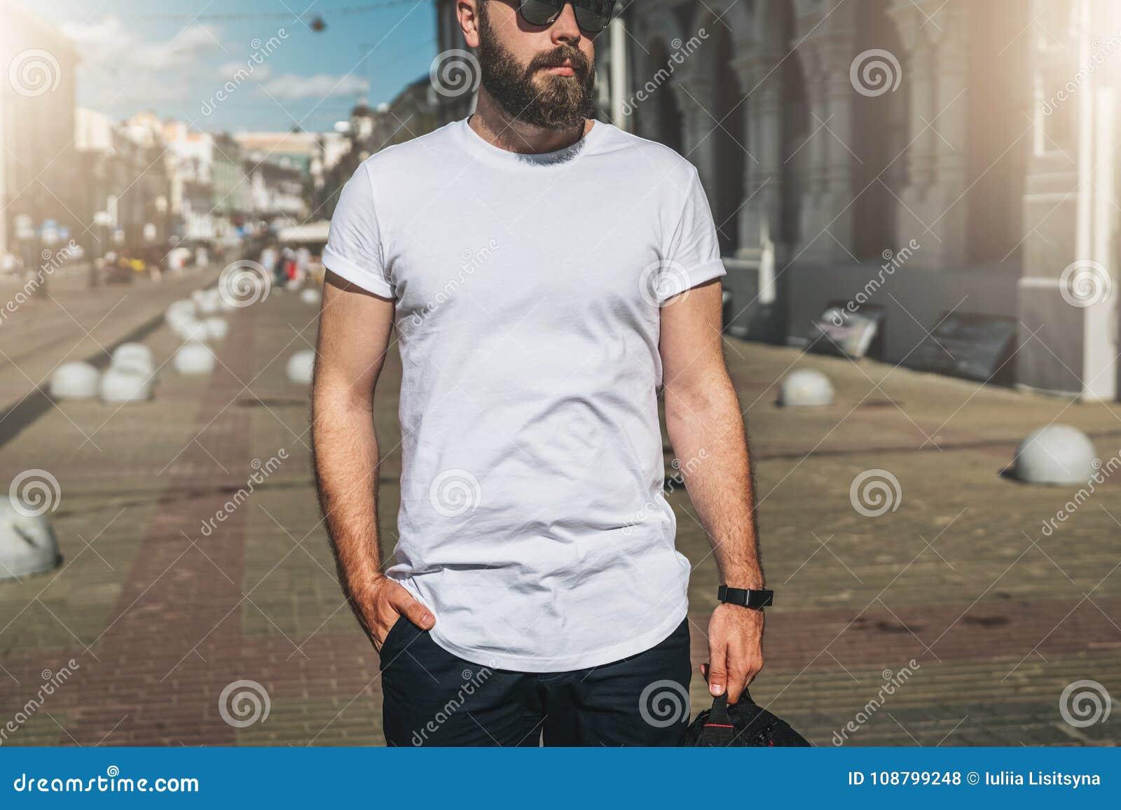 Bekläda beskådar Barnet uppsökte den millennial t-skjortan för iklädd vit för mannen, och solglasögon är ställningar på stadsgata