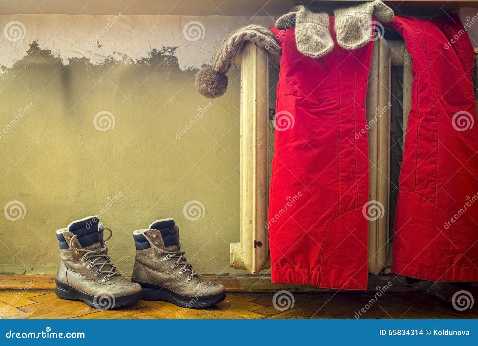 Beklär att hänga på ett varmt gammalt element, som ställningar skor bredvid