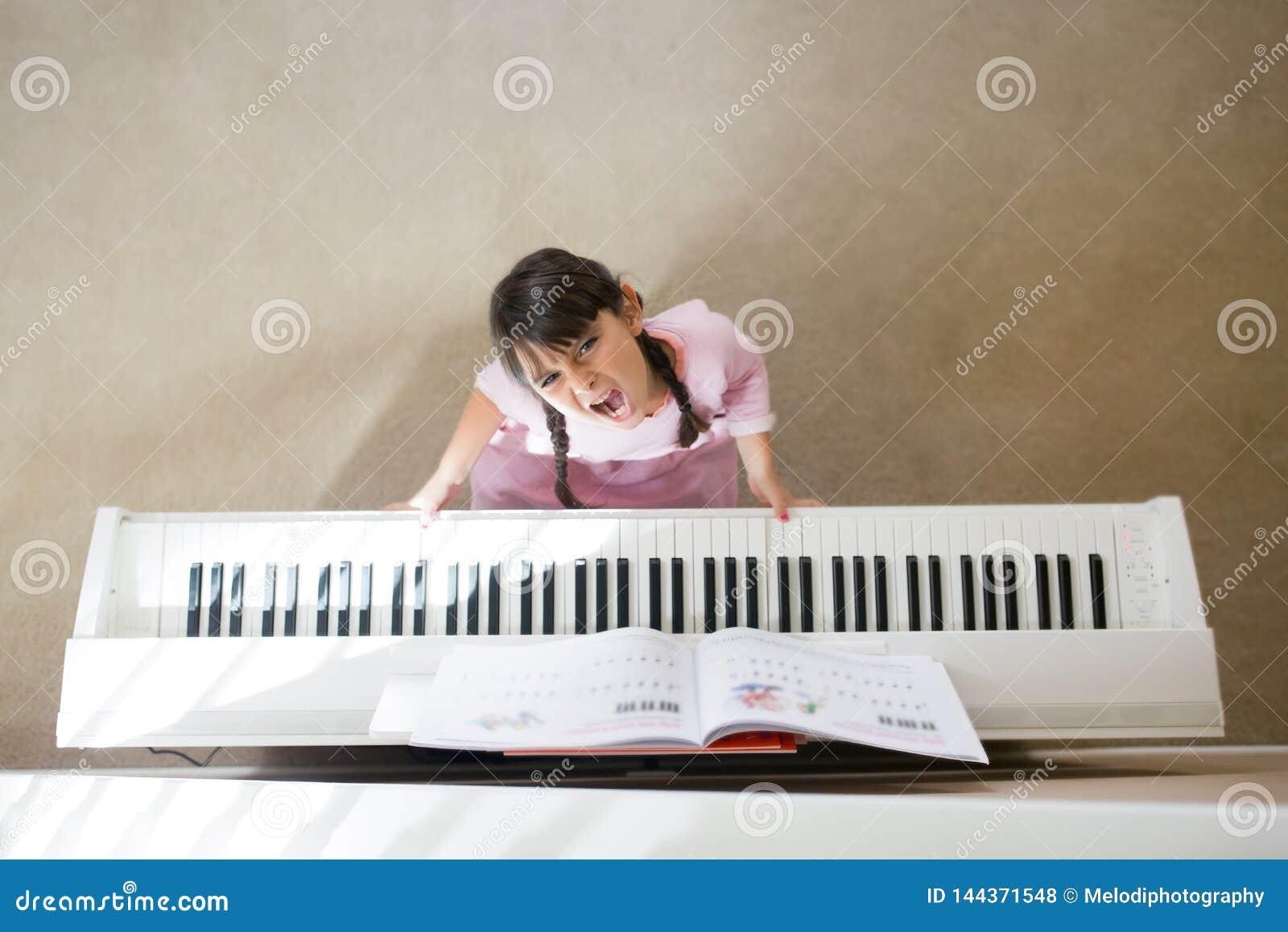 Beklemtoonde meisje het spelen piano