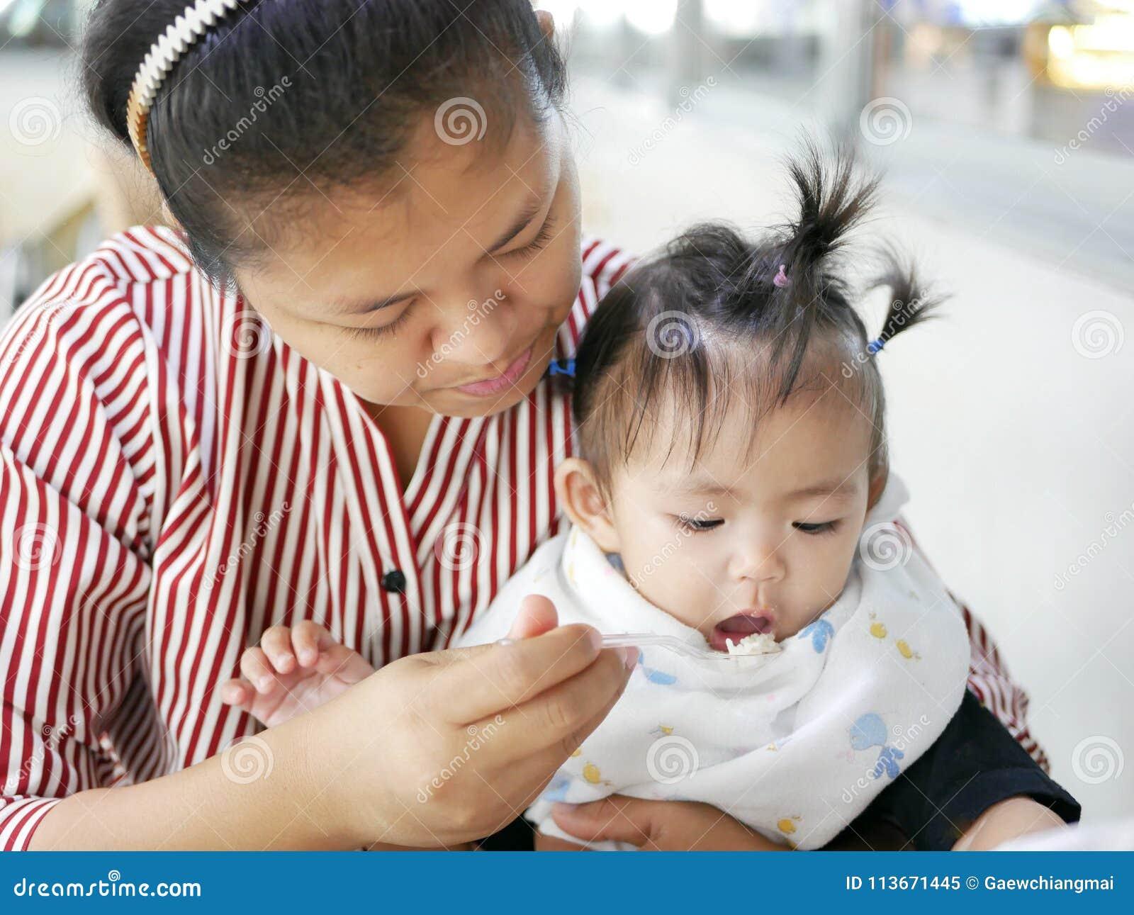 Bekwame Aziatische moeder die kleine lepel gebruiken om haar babymeisje, 12 maanden oud, bij een cafetaria te voeden