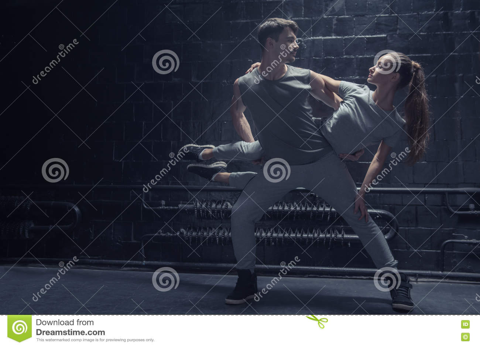 Bekwame dansers die in de donkere aangestoken ruimte presteren