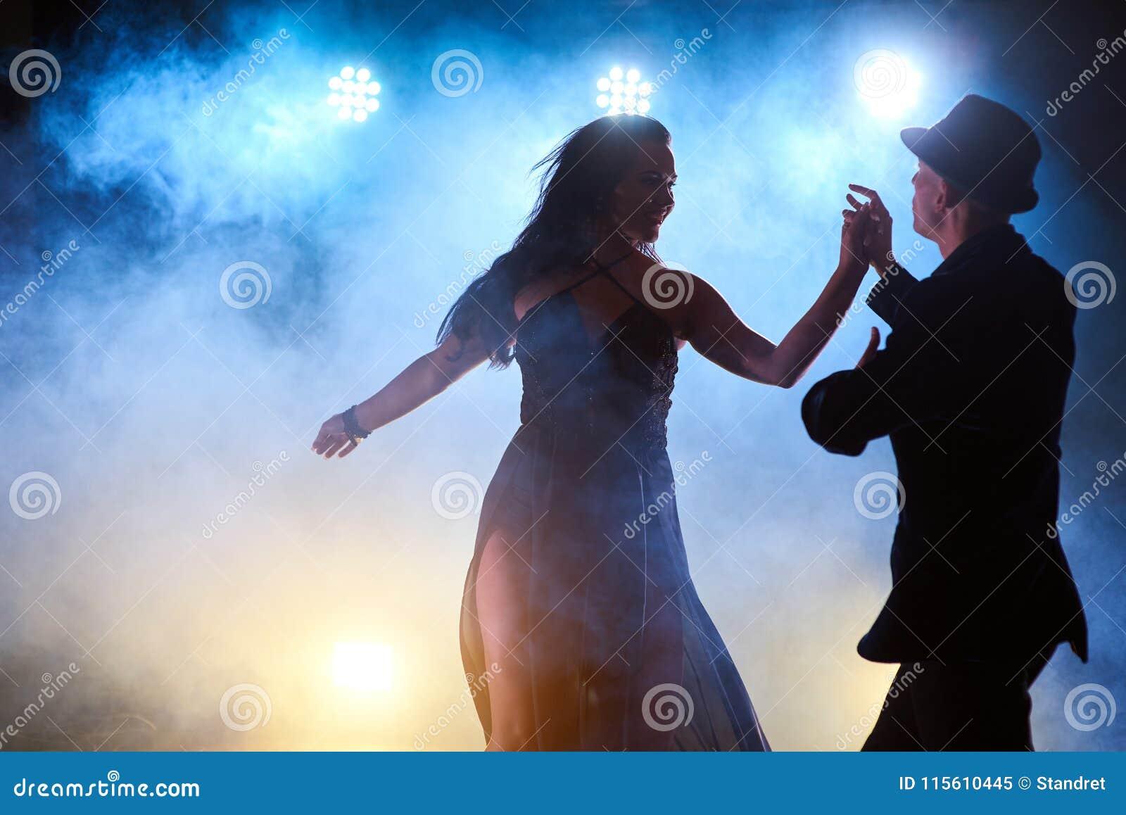 Bekwame dansers die in de donkere ruimte onder het de overleglicht en rook presteren Sensueel paar die artistiek uitvoeren