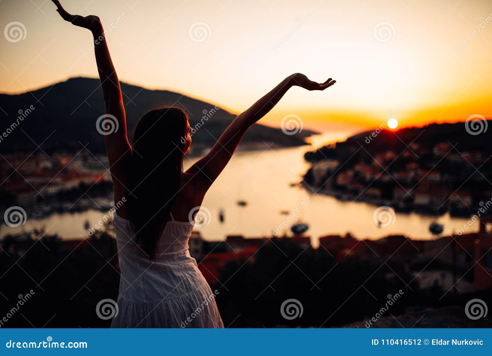 Bekymmerslös kvinna som tycker om i naturen, härligt rött solnedgångsolsken Finna inre fred Andlig läka livsstil Tycka om fred, m