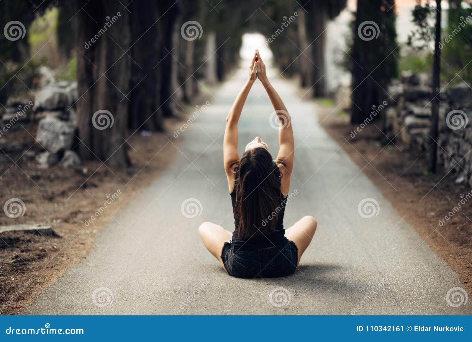 Bekymmerslös lugna kvinna som mediterar i natur Finna inre fred Man att göra hälften som viker i sittande lotusblommapos Andlig l