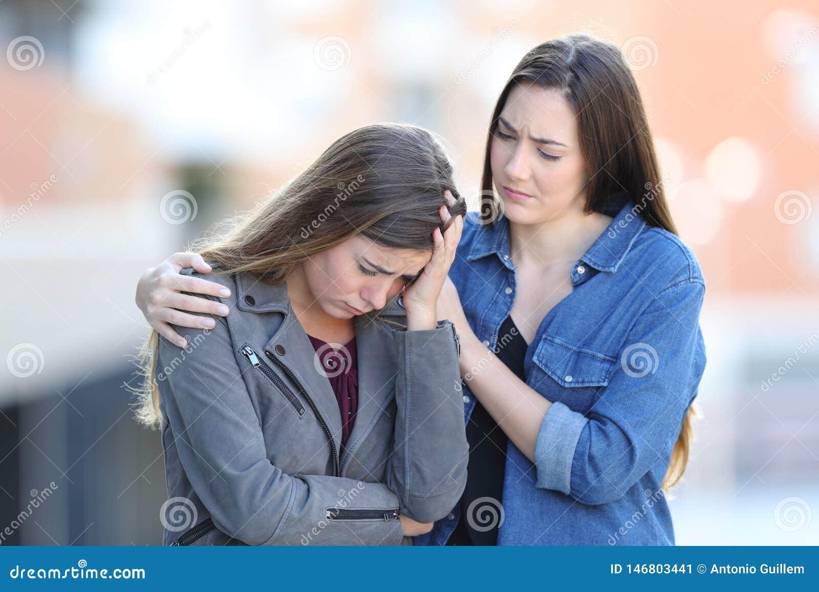 Bekymrad kvinna som tröstar hennes ledsna vän i gatan
