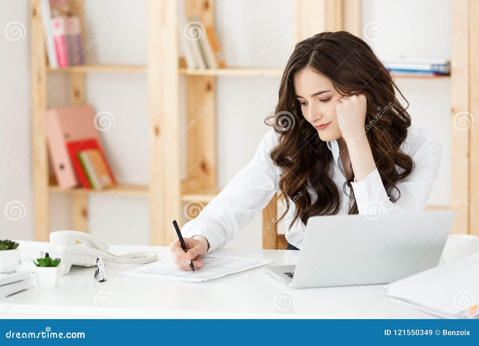 Bekymrad ung affärskvinna som arbetar med dokumentet på det moderna kontoret
