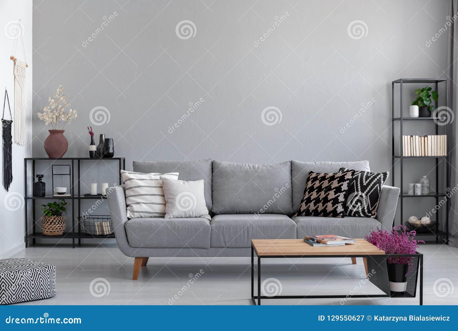 Belägga med metall svarta hyllor med böcker, stearinljus och växter bak den gråa soffan med mönstrade kuddar, verkligt foto med k