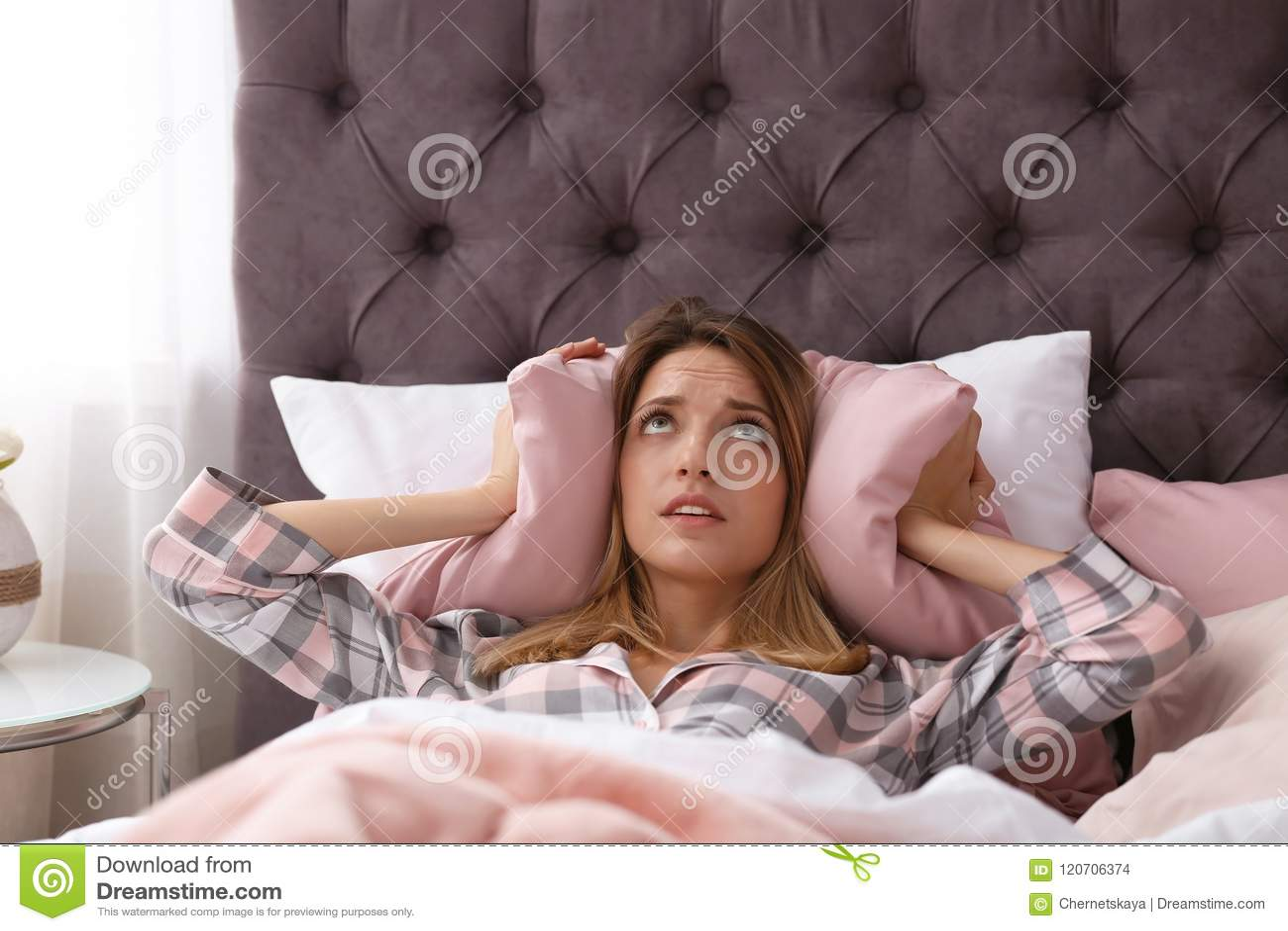 Beläggning för den unga kvinnan gå i ax med kudden, medan försöka att sova i säng hemma