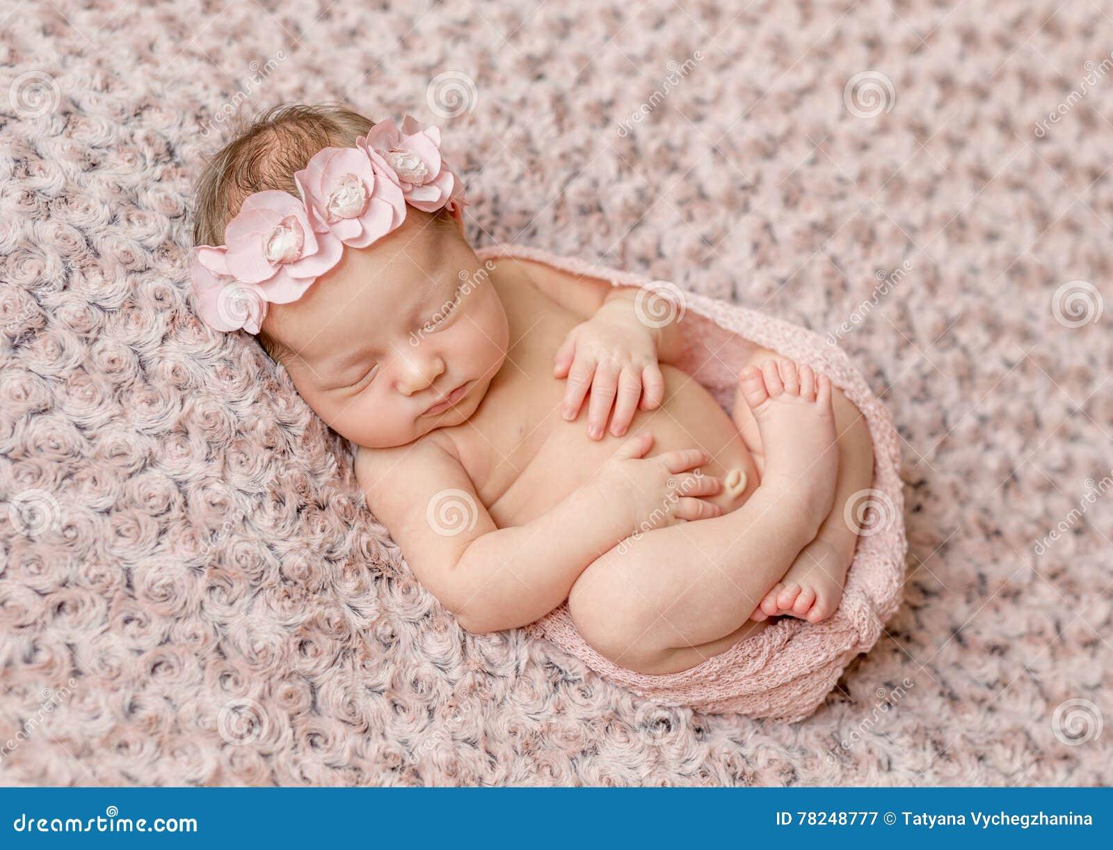 Bel courbé endormi nouveau-né, enveloppé dans la couche-culotte rose