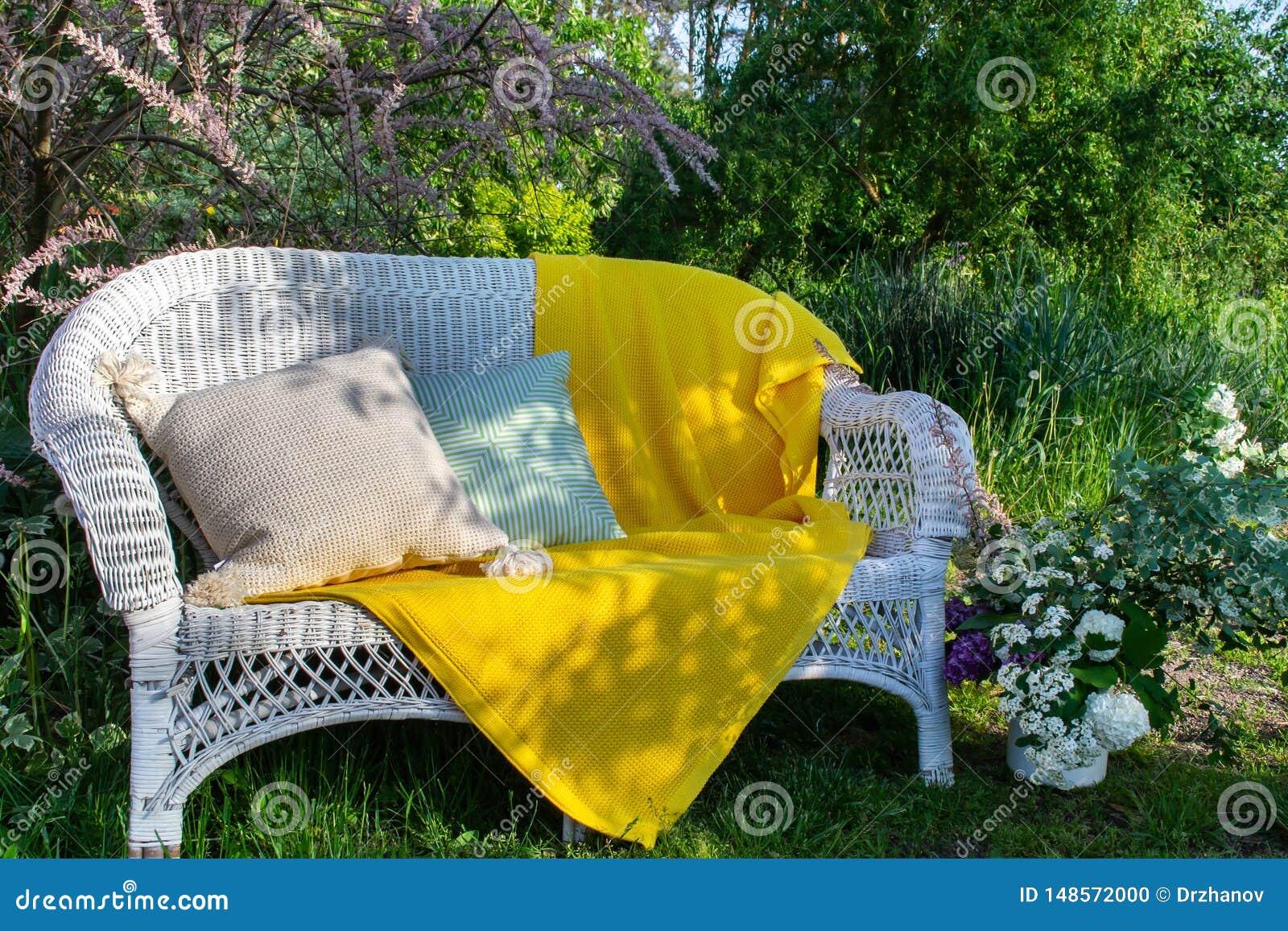 Bel endroit pour le repos dans le jardin vert - divan en osier blanc avec la couverture jaune-jaune et deux coussins différents
