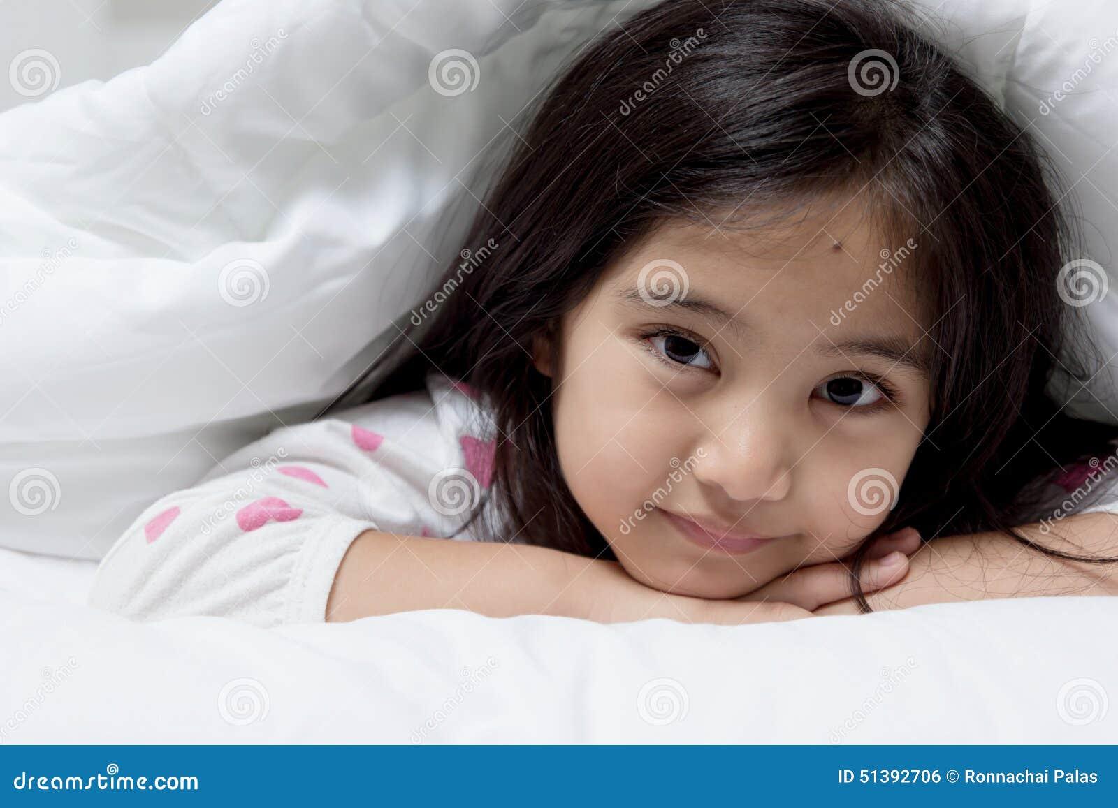 Bel enfant asiatique fixant sur le lit