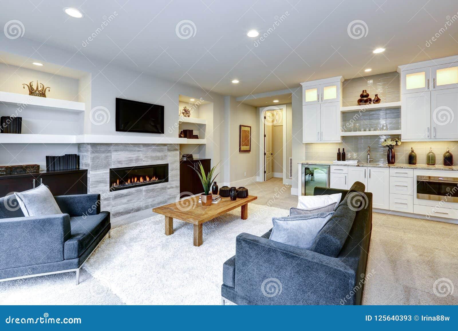 Bel intérieur moderne de salon avec le mur en pierre et le firepl