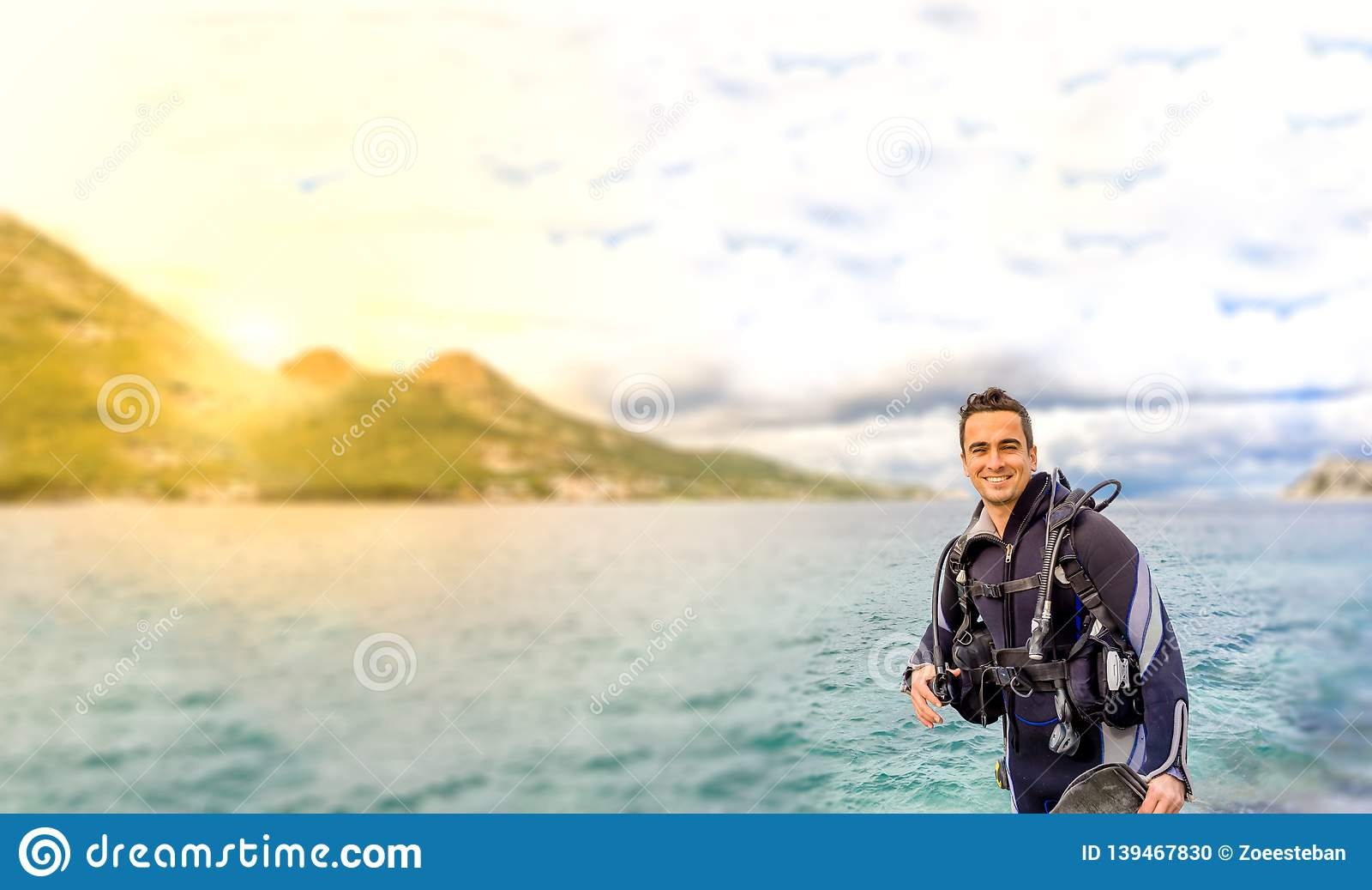 Bel sourire de plongeur d isolement jeune par homme prêt à aller plongée à l air en vêtement isothermique d eau froide, ailerons,