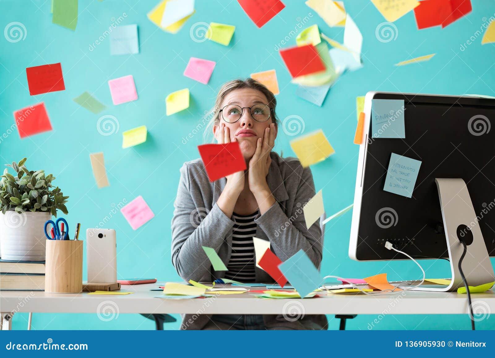 Belastad ung affärskvinna som ser upp omgiven av stolpe-i kontoret