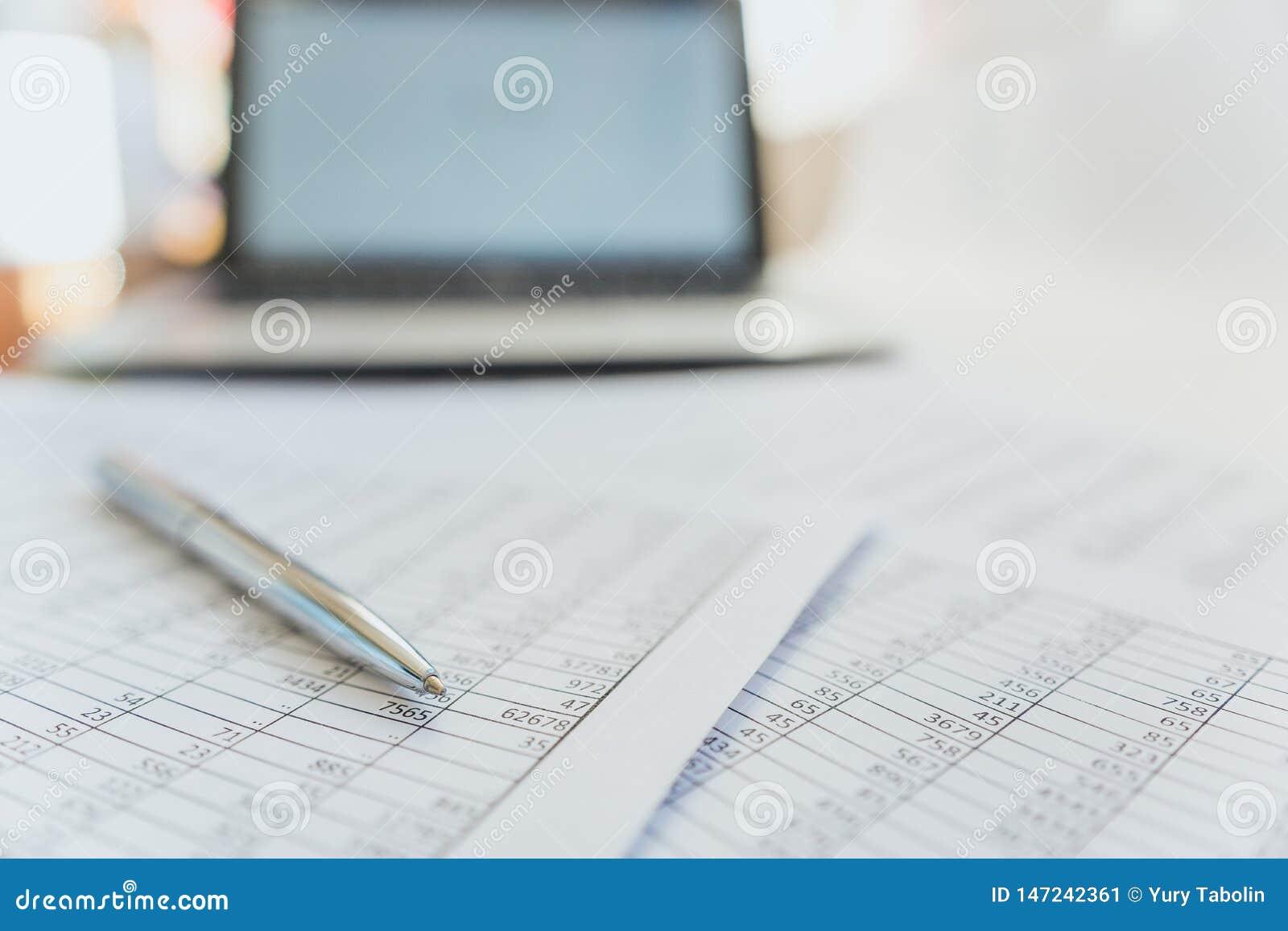 Belastingen en boekhouding Samenvattende tabel Pen en notitieboekje op documenten met berekeningen