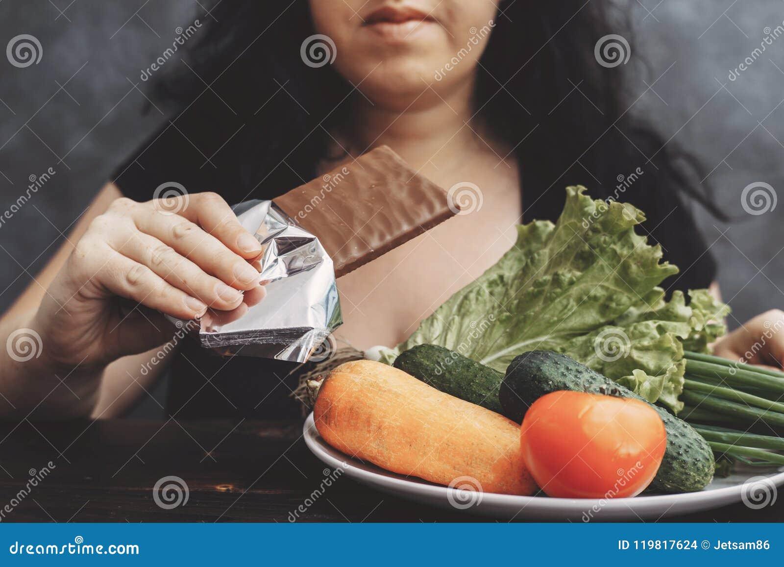 Beleibte Frau, welche die Schokolade ablehnt gesundes Lebensmittel isst