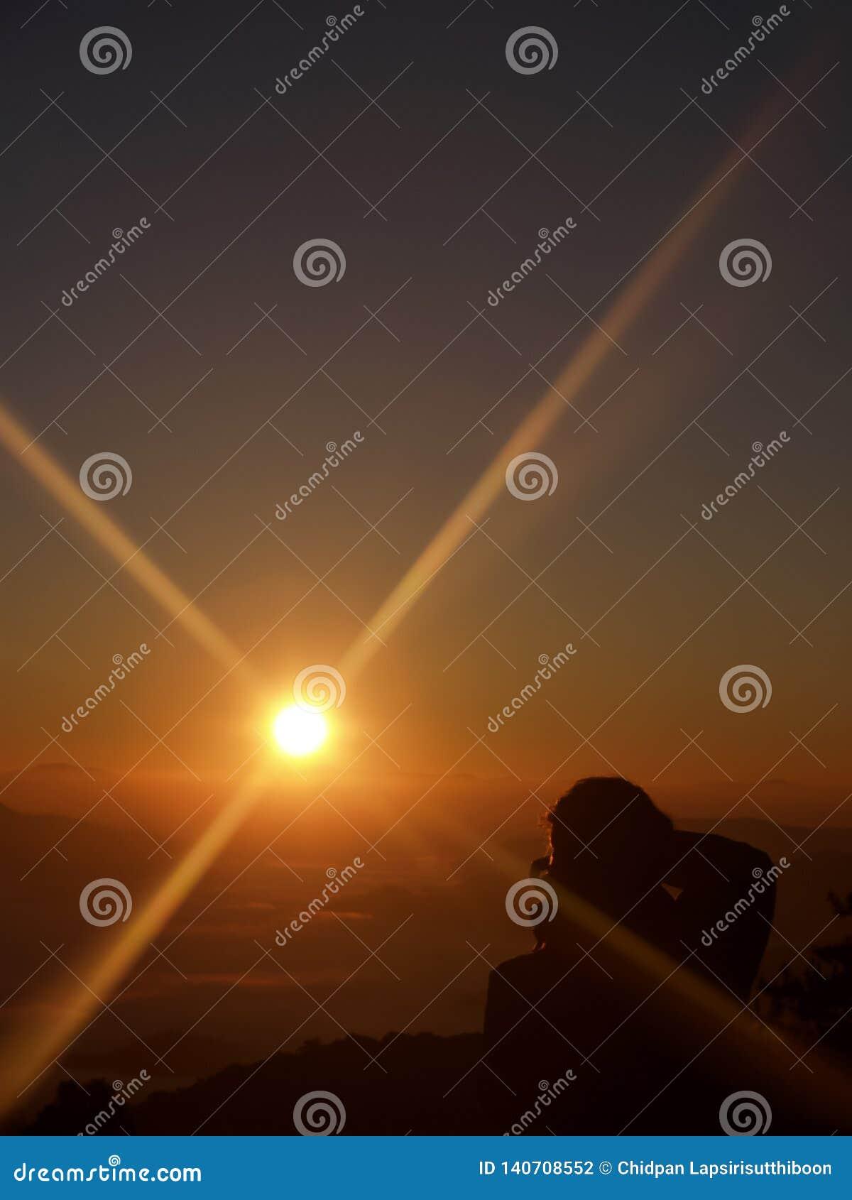 A beleza dos nasceres do sol e o céu na manhã E um fotógrafo da parte traseira estava disparando No ponto de vista