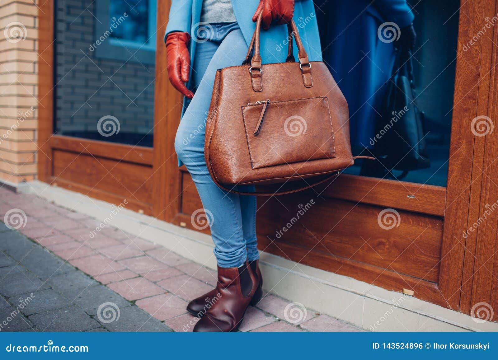 Beleza e fôrma Revestimento vestindo à moda e luvas da mulher elegante, guardando a bolsa marrom do saco