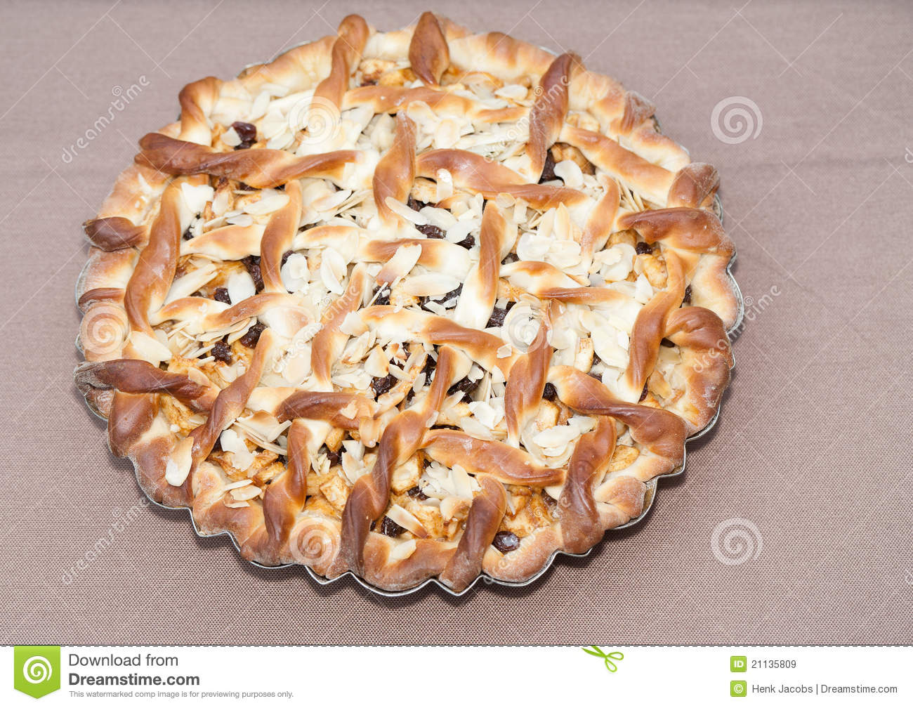 An outdoors top closeup of a homemade Belgian apple-raisin pie topped ...