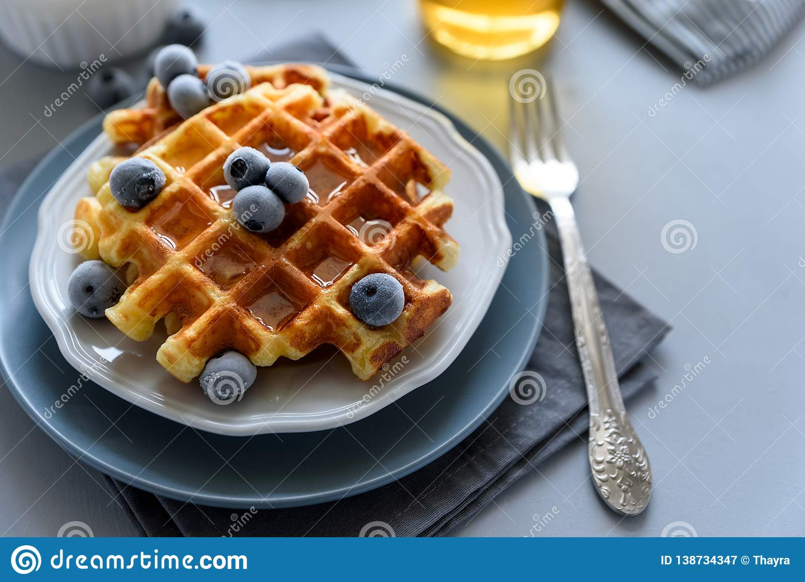 Belgian waffles with blueberries and honey on gray wooden background. Homemade healthy breakfast. Selective focus