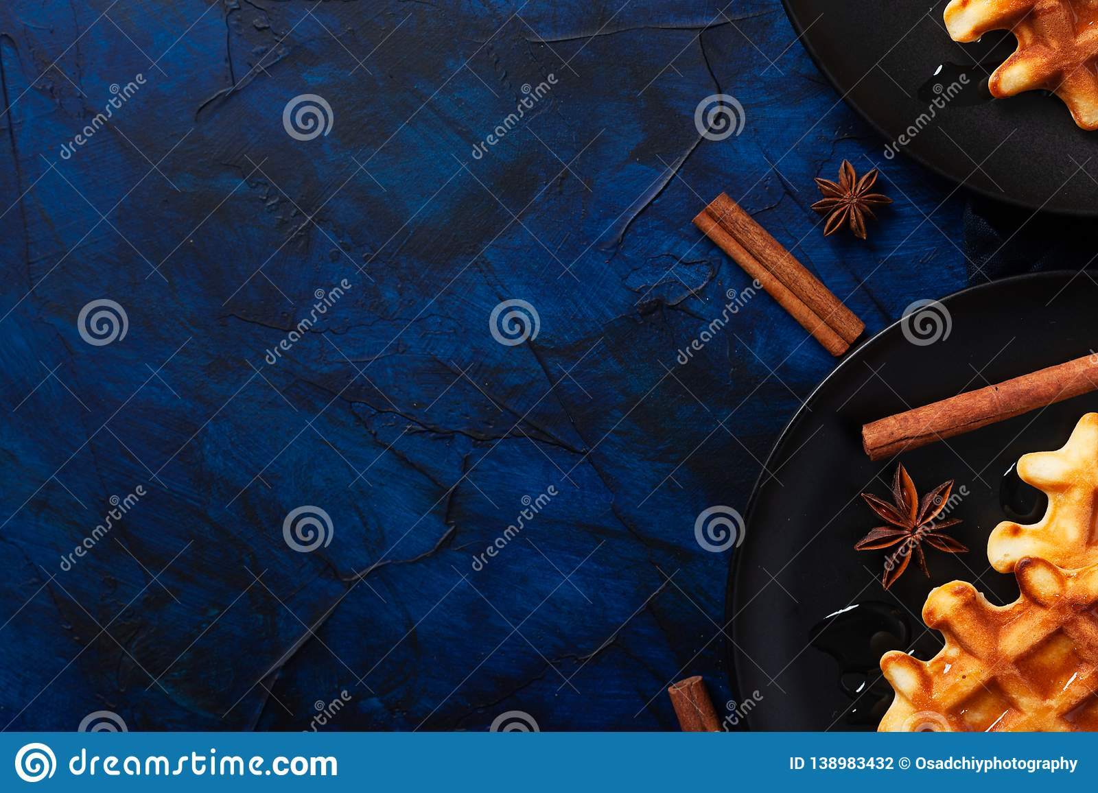 Belgian waffles with cinnamon and anise on dark blue textured background