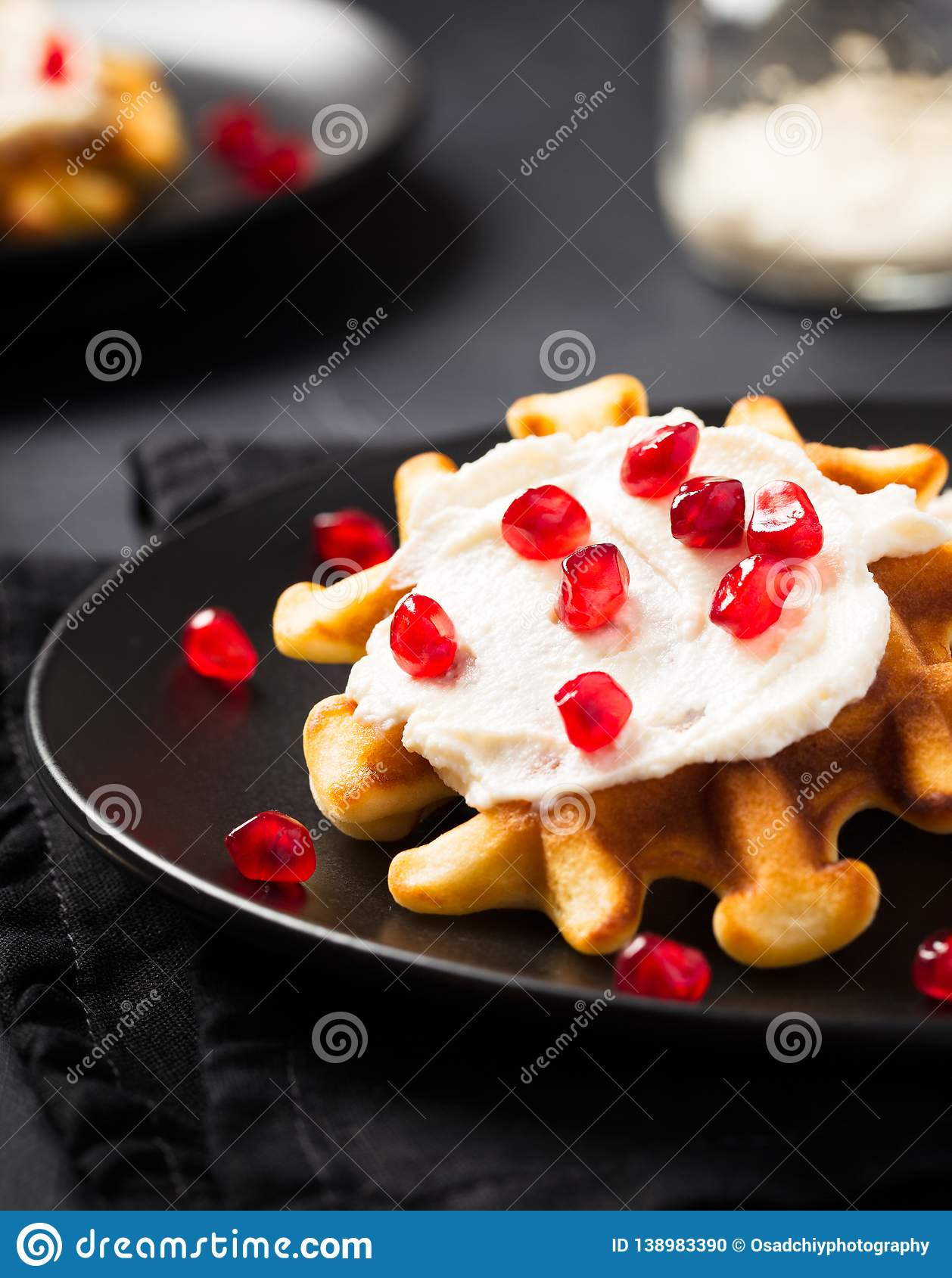 Belgian waffles with cream and pomegranate seeds on black background
