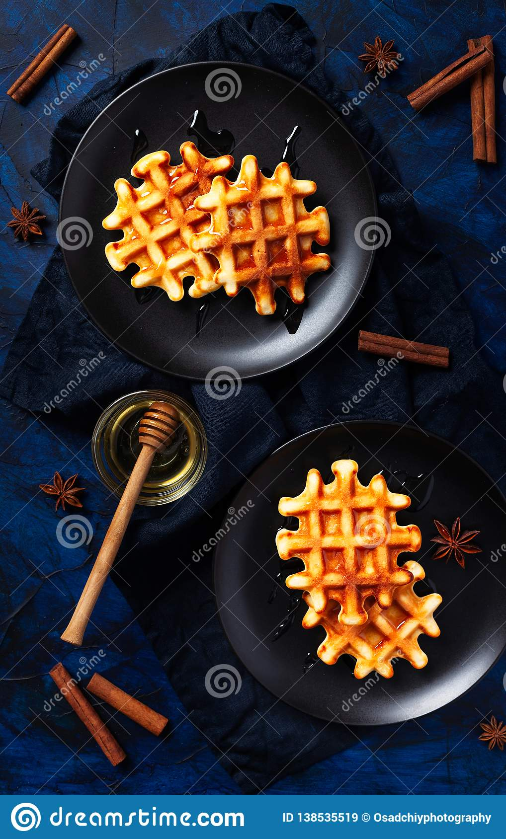 Belgian waffles with honey and cinnamon on dark blue textured background - fresh baked pastry with spices