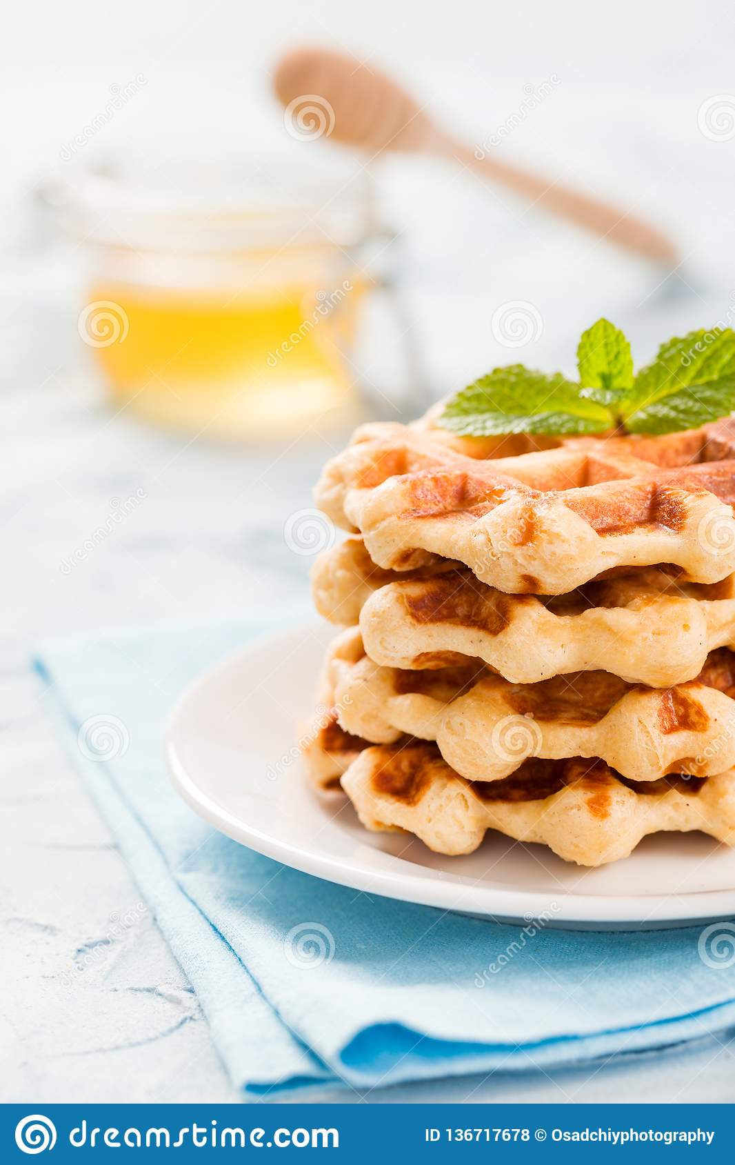 Belgian waffles with mint leaves and honey in glass jar with wooden honey dipper on pastel blue background.