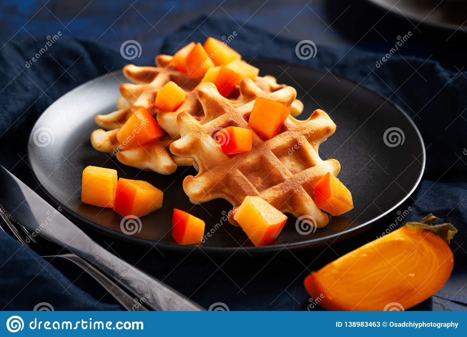 Belgian waffles with persimmon on black plate in dark mood style
