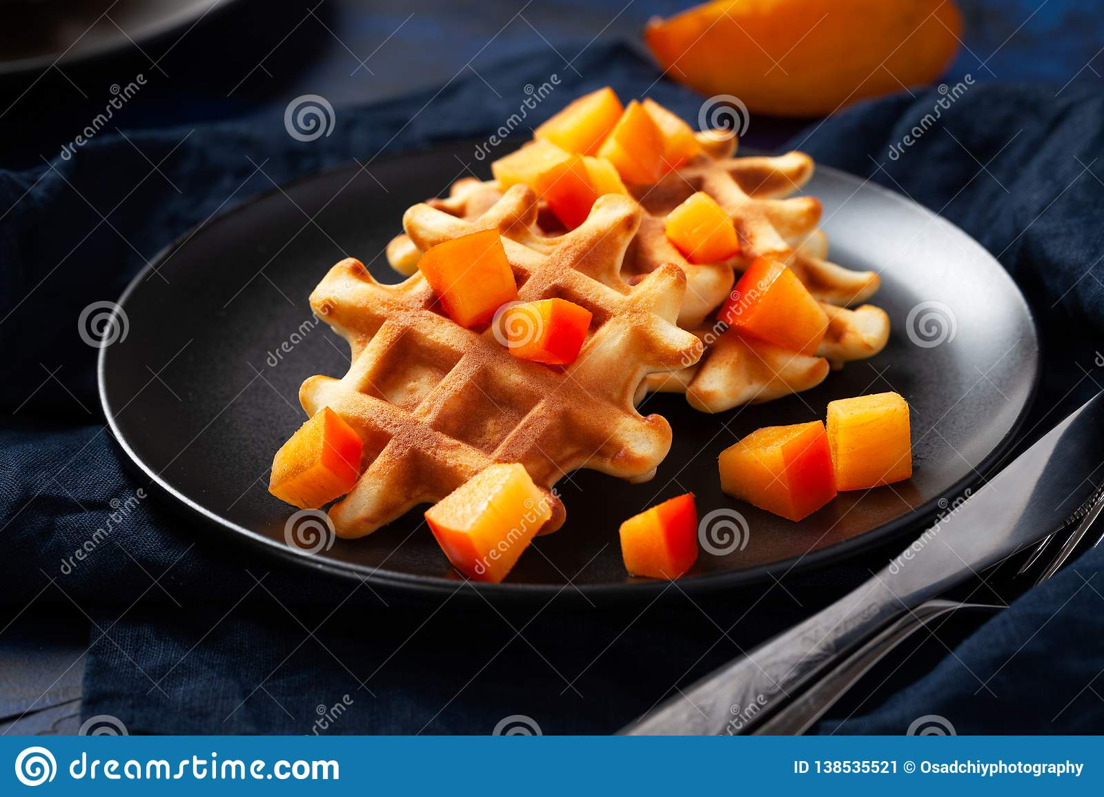 Belgian waffles with persimmon on black plate in dark mood style - close up horizontal photography