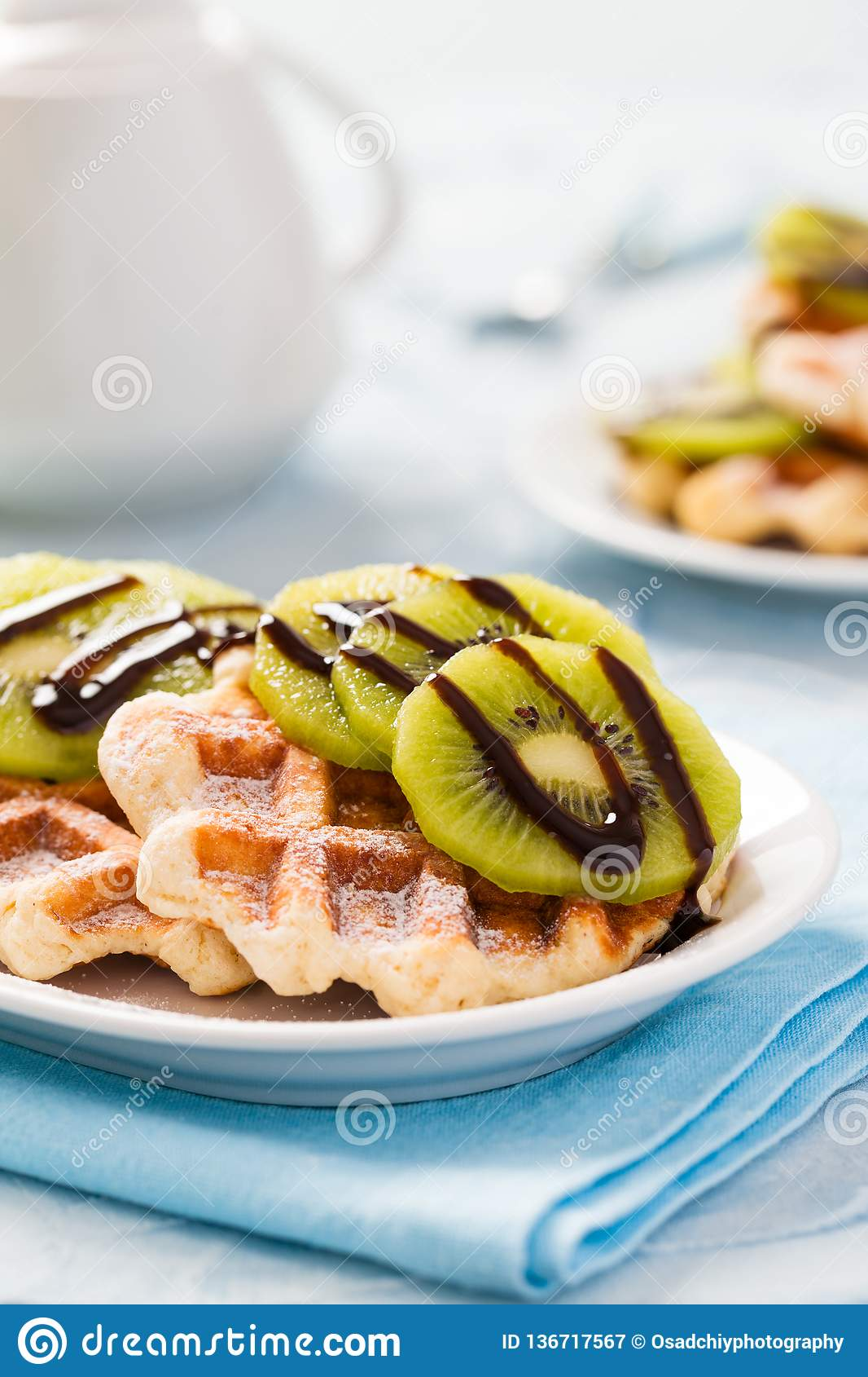 Belgian waffles with sliced kiwi fruit, sugar powder and chocolate syrup with teapot of hot drink.